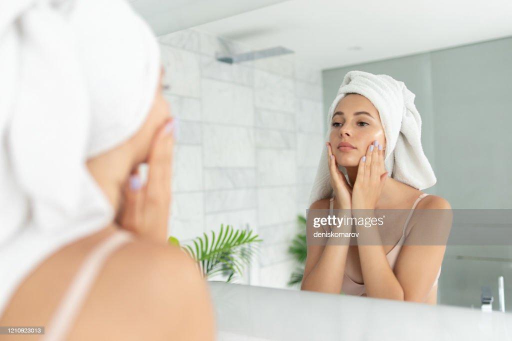 Jonge mooie vrouw die huidgezichtscrèmelotion gebruikt : Stockfoto