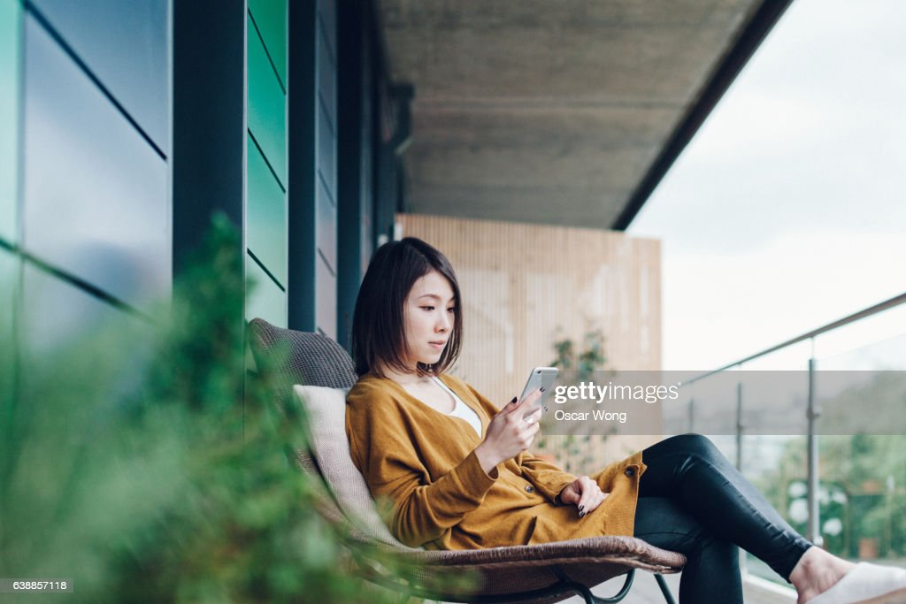 Young beautiful woman using smartphone in balcony : Stock Photo