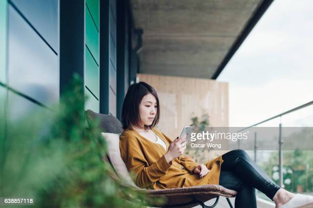 Young beautiful woman using smartphone in balcony