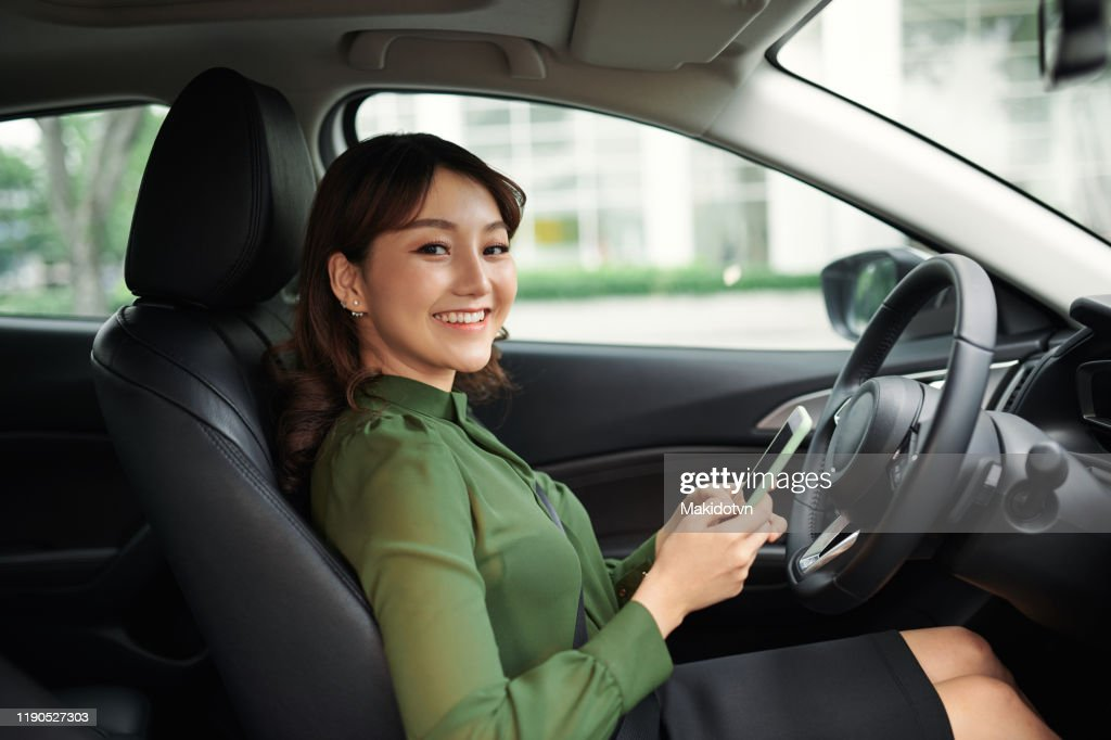 車の運転中にスマートフォンを使用して若い美しい女性 : ストックフォト