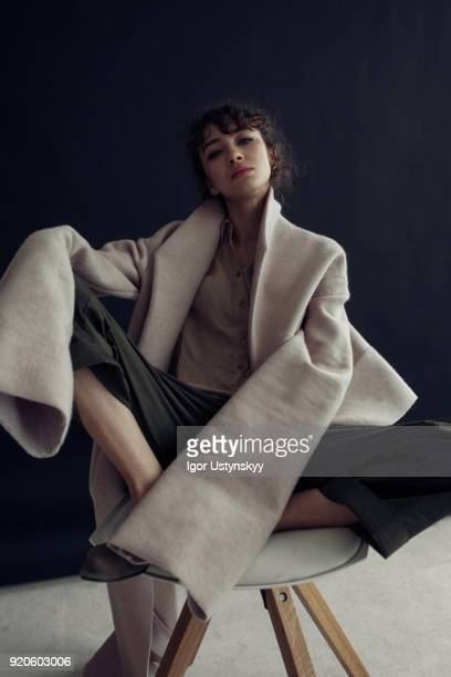 young beautiful woman wearing beige coat - smug stock photos and pictures