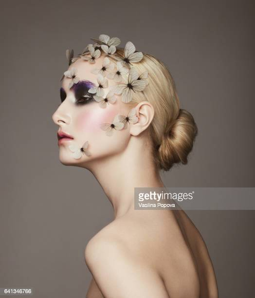 Young beautiful woman with butterflies on her face