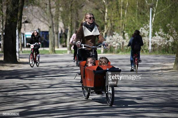 Young beautiful woman with children riding bicycle in Amsterdam