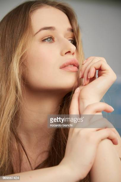 young beautiful woman with long hair thinking and posing with hands
