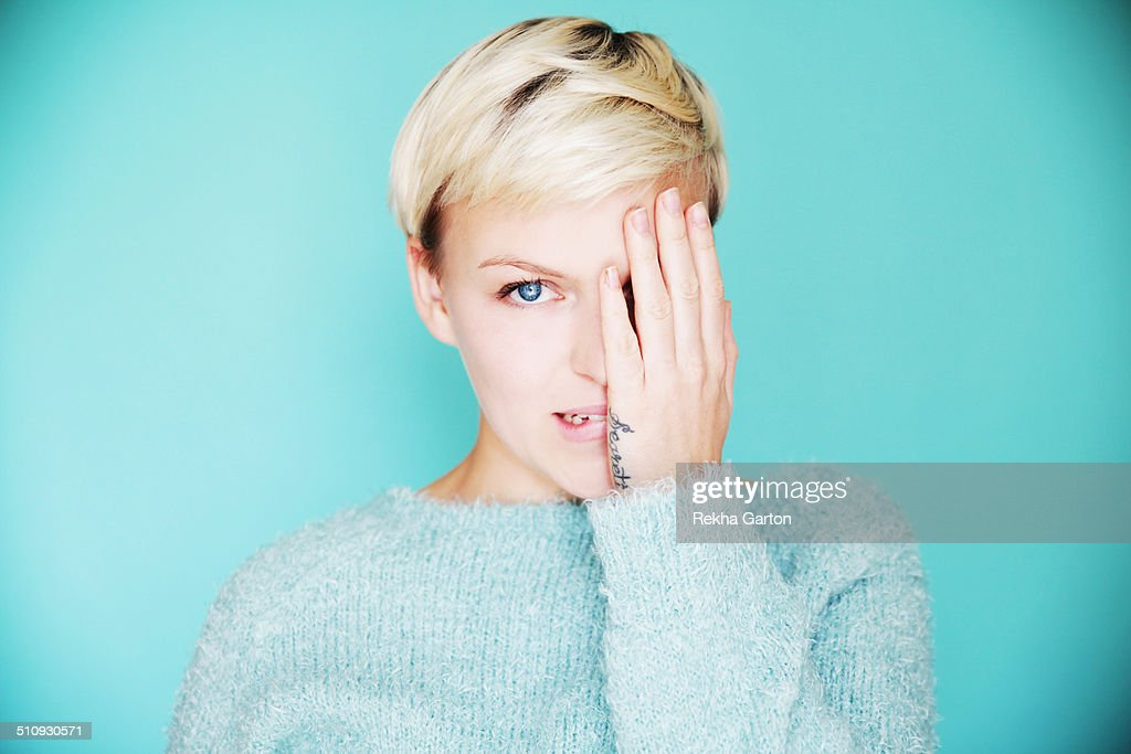 Young beautiful woman with one hand over one eye