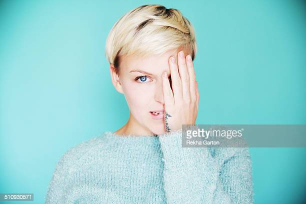 young beautiful woman with one hand over one eye - biting lip stock pictures, royalty-free photos & images