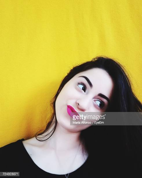 young beautiful woman with pink lipstick and long hair against yellow wall - batom rosa - fotografias e filmes do acervo