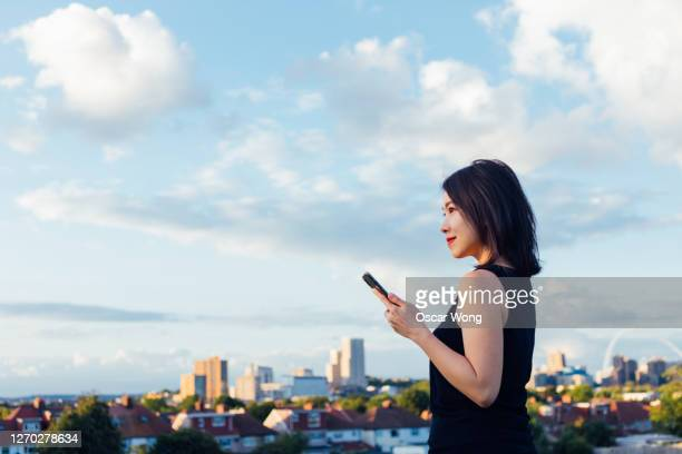 young beautiful woman with smart phone against blue sky - side view stock pictures, royalty-free photos & images