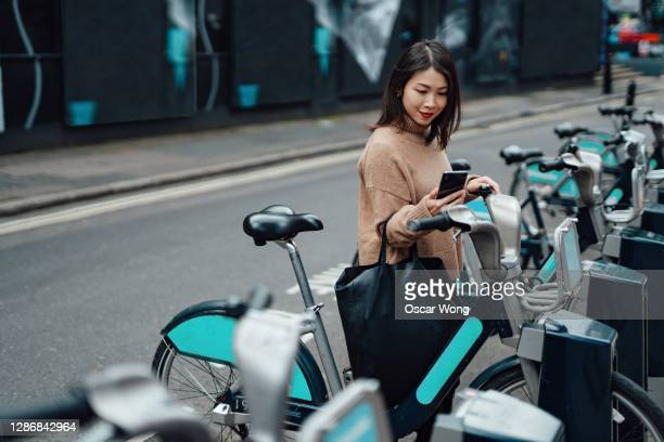 young beautiful woman with smartphone renting bicycle from bike share service in the city - street stock pictures, royalty-free photos & images