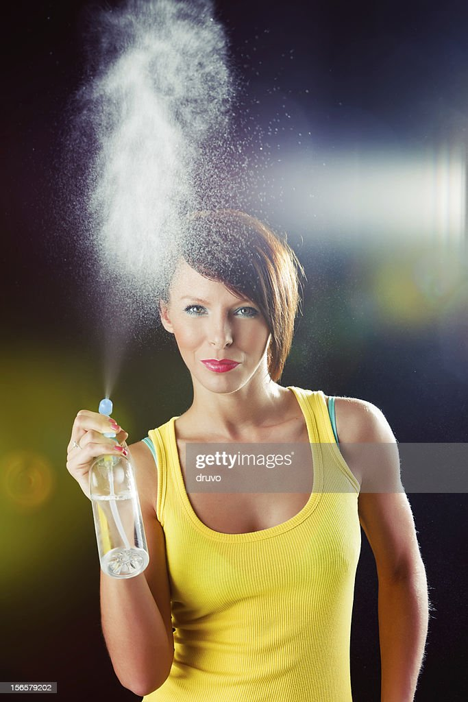 Young beautiful woman with spray bottle : Stock Photo