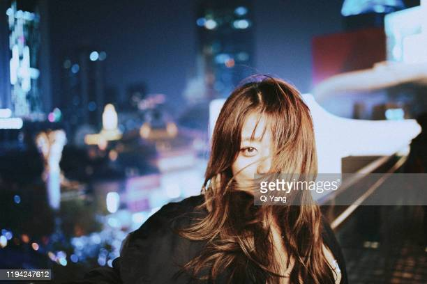 young beautiful woman with wavy hair in the city at night - glamour stock-fotos und bilder
