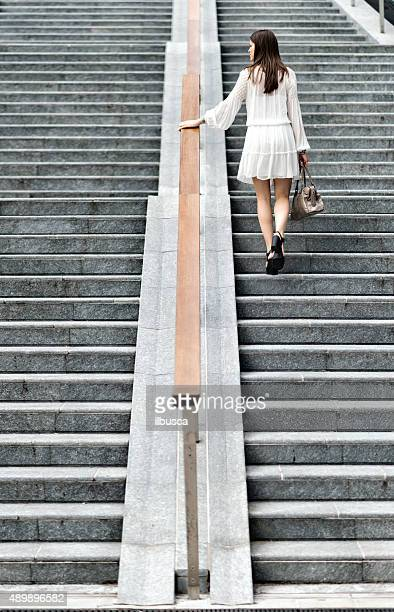 Young beautiful woman with white dress on modern staircase