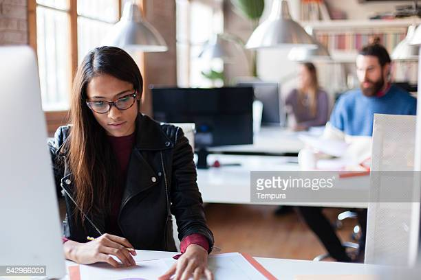 Young beautiful woman working in small office