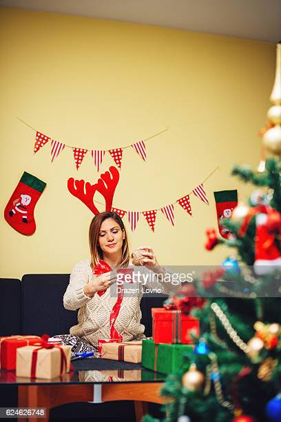 Young beautiful woman wrapping Christmas gifts