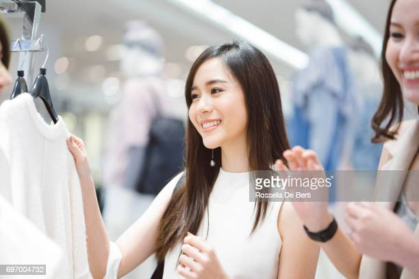 Young beautiful women shopping together in clothing store, smiling