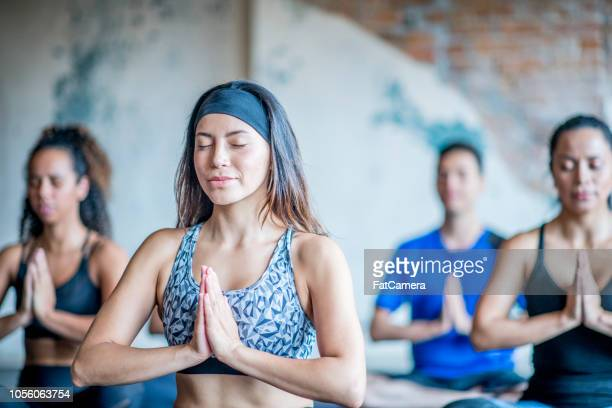young beautiful women sits in yoga pose with eyes closed. - headband stock pictures, royalty-free photos & images