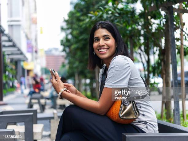 young beautiful women using phone at street - ibnjaafar stock photos and pictures