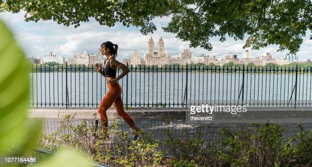 young beautiful young woman running around central park, new york - central park manhattan stock pictures, royalty-free photos & images
