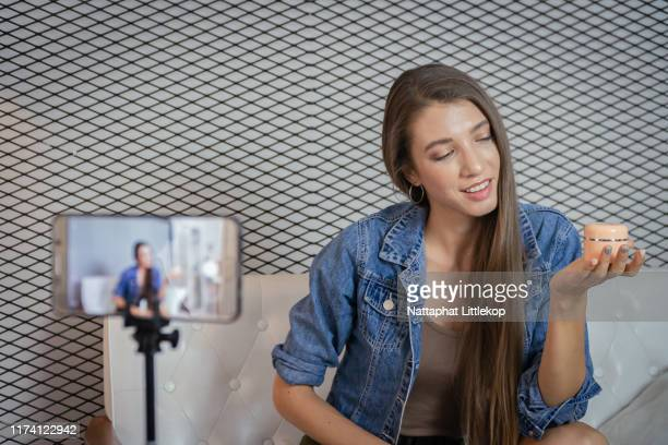 young beauty blogger selling her cosmetic on live stream broadcasting by mobile phone. - live broadcast stock pictures, royalty-free photos & images