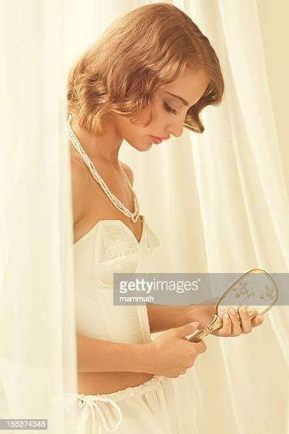 Jeune beauté à côté de la fenêtre en tenant une brosse à cheveux
