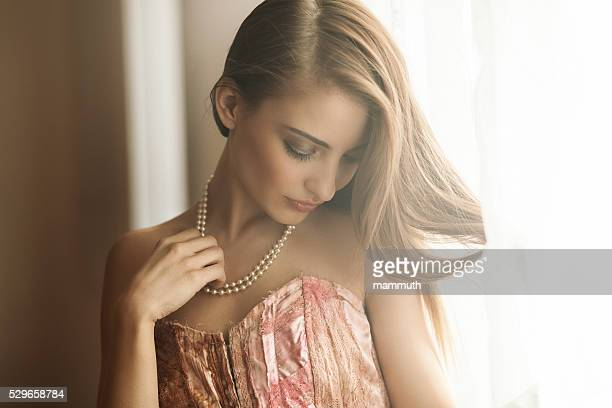 young beauty by the window - necklace stock pictures, royalty-free photos & images