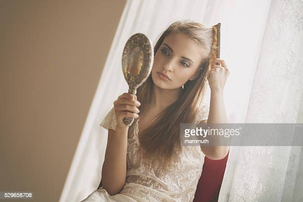 young beauty combing her hair