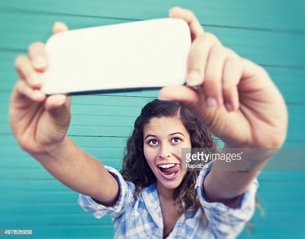 Junge Schönheit sticks Ihre Zunge für hübsche, lustige selfie