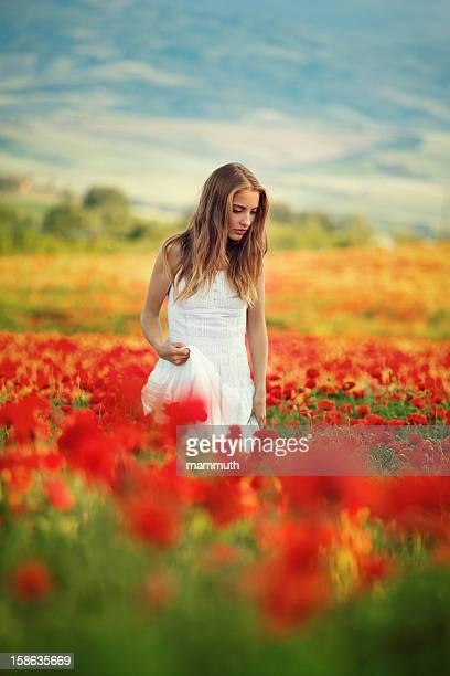 Junge Schönheit, die zu Fuß in Mohn-Feld