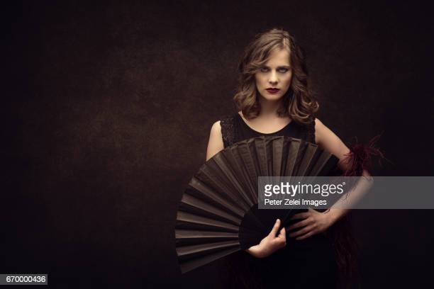 Young beauty with hand fan and feather boa