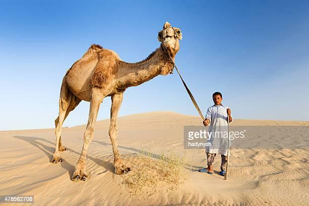 Young beduino con camellos en el desierto del sáhara del oeste en África