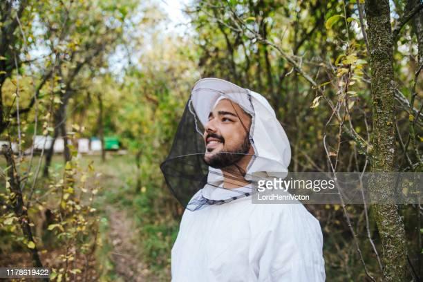 防護服を着た若い養蜂家 - 養蜂 ストックフォトと画像