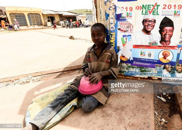 TOPSHOT A young beggar sit with a bowl beside poster of candidate of the ruling All Progressives Congress President Mohammadu Buhari and Vice...