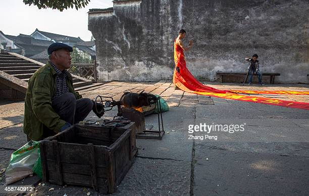 WUZHEN TONGXIANG ZHEJIANG CHINA A young behavior artist performs beside an old man who is making popcorn in a Chinese traditional way The second...