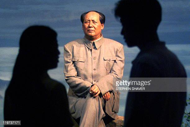 Young Beijingers talk while viewing a wax model of China's late chairman Mao Zedong sitting on a tree stump in the mountains on display at the Museum...