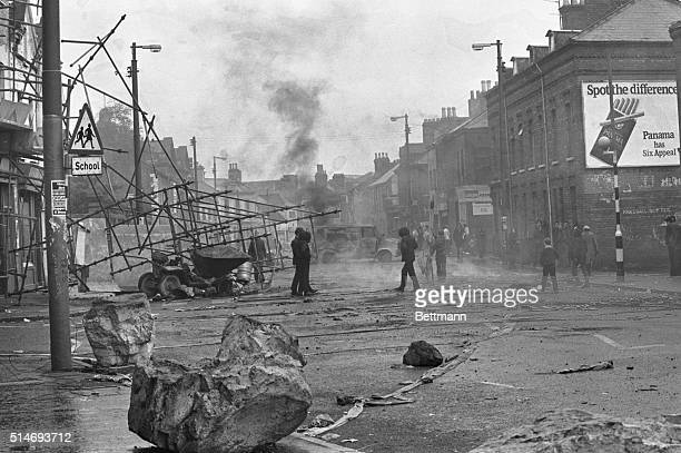 Young Belfast men gather around burning vehicles in a debris-strewn Belfast street. The fires were set as a harassment tactic against the British...