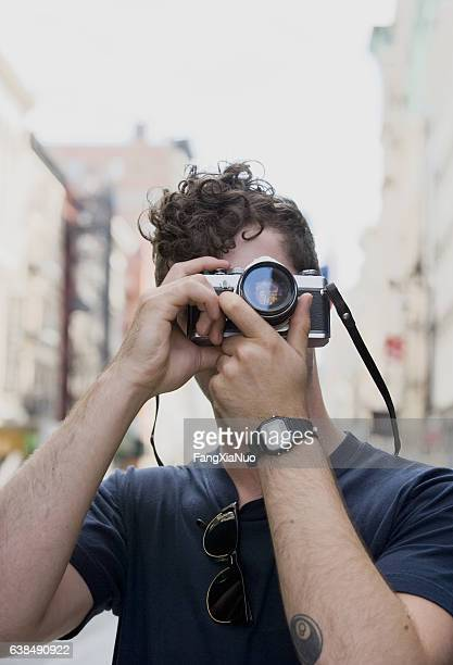 young belgian man taking photograph in downtown city - new yorker building stock photos and pictures