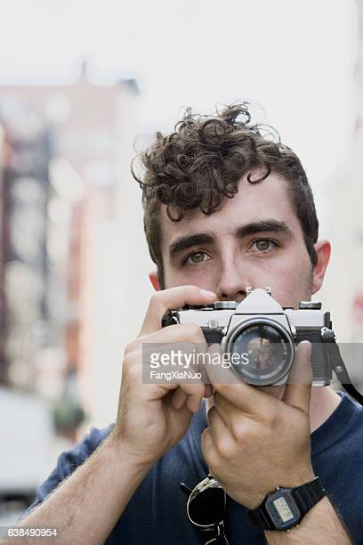 young belgian man taking photograph in downtown city - divergent film stock photos and pictures