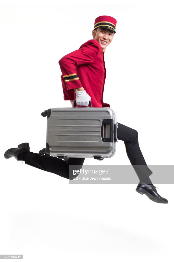 Young bellboy carrying suitcases : Stock Photo