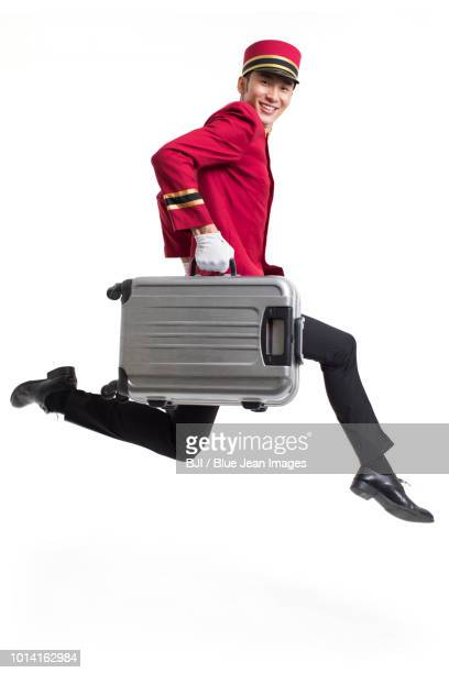young bellboy carrying suitcases - doorman stock photos and pictures