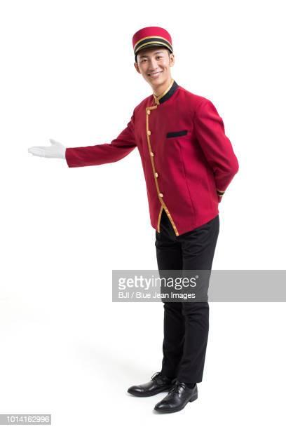 young bellboy greeting - ホテルマン ストックフォトと画像