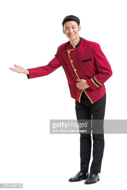young bellboy greeting - doorman stock photos and pictures