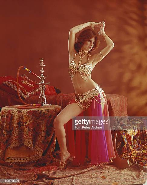 young belly dancer dancing beside hookah on table - belly dancing stock photos and pictures