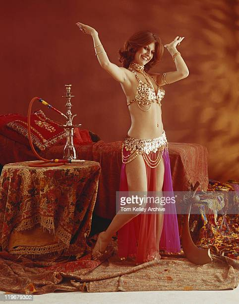 young belly dancer dancing beside hookah on table, smiling - belly dancing stock photos and pictures
