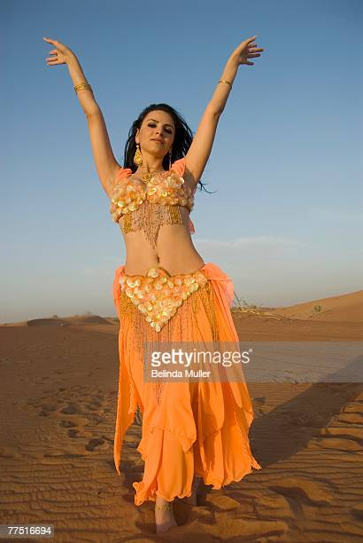 young belly dancer dancing in the desert. hatt desert, dubai, united arab emirates - belly dancing stock photos and pictures