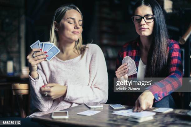 young best girls  friends playing game card at home. - playing cards stock photos and pictures