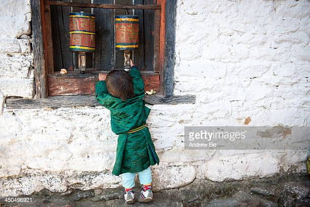 CONTENT] A young Bhutanese boy in traditional costume the Gho a kneelength robe somewhat resembling a kimono that is tied at the waist by a...