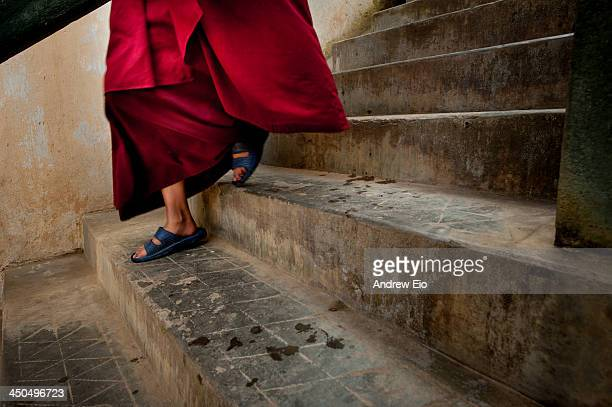 Young Bhutanese monk comes down a series of concrete steps wearing a saffron red robe and blue sandals. The steps are worn and aged. The steps are at...
