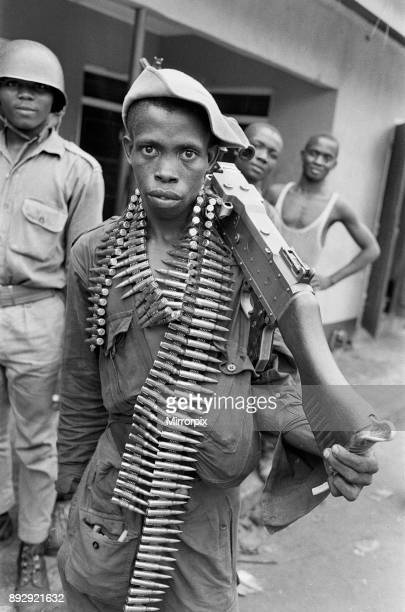 A young Biafran soldier seen here posing with a heavy machine gun and ammunitaion belt draped around his neck 11th June 1968