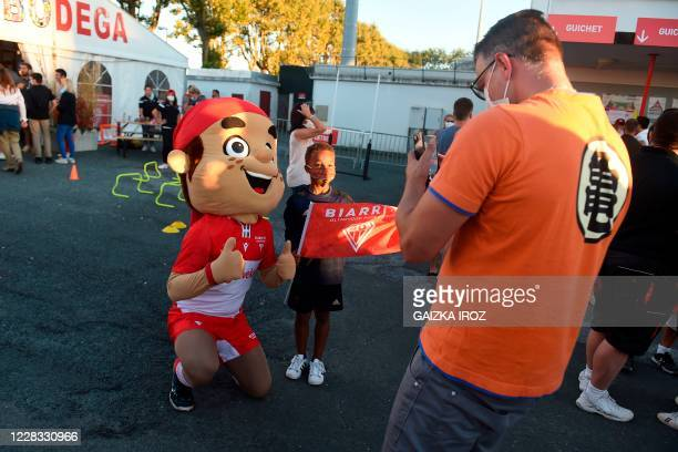 Young Biarritz rugby fan, wearing a protective mask, poses with BOPB mascot Koxka before the first French Pro D2 Championship official rugby match...