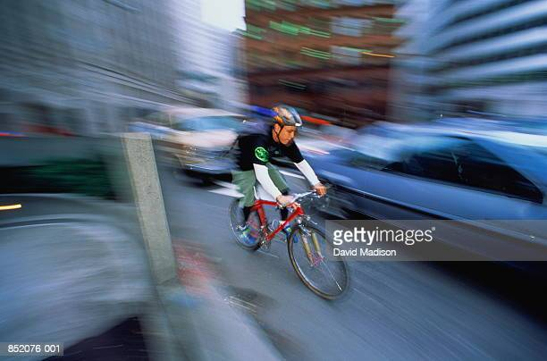 young bicycle messenger riding on urban street (blurred motion) - bicycle messenger stock pictures, royalty-free photos & images